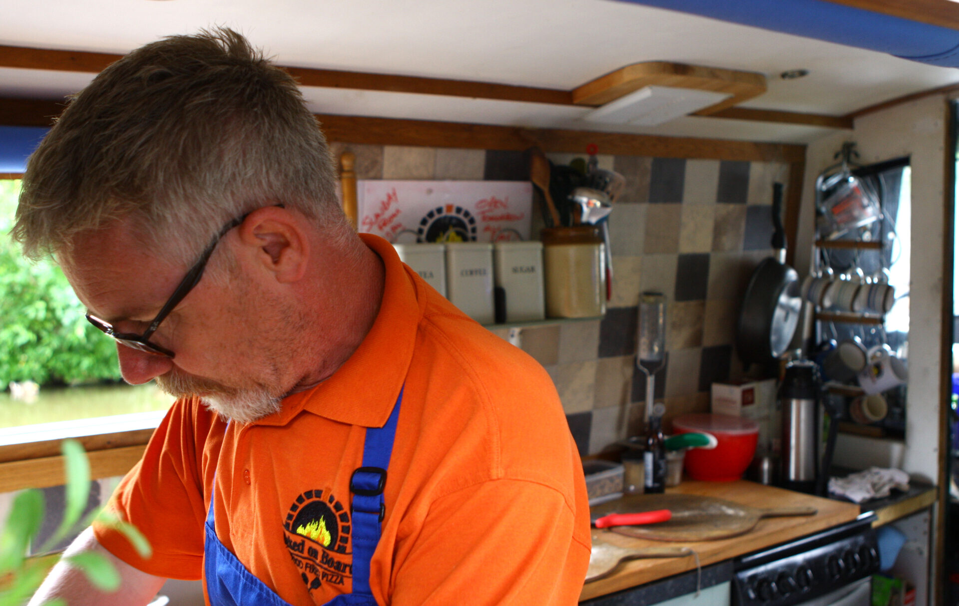 """This chap was busy feeding us all delicious fresh pizza from his """"BAKED ONBOARD"""" pizza oven boat. Check out his galley !"""