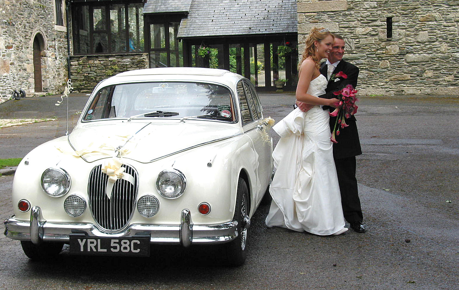 Caroline and Allan, now Mr. and Mrs. with their white Jaguar, wedding car.
