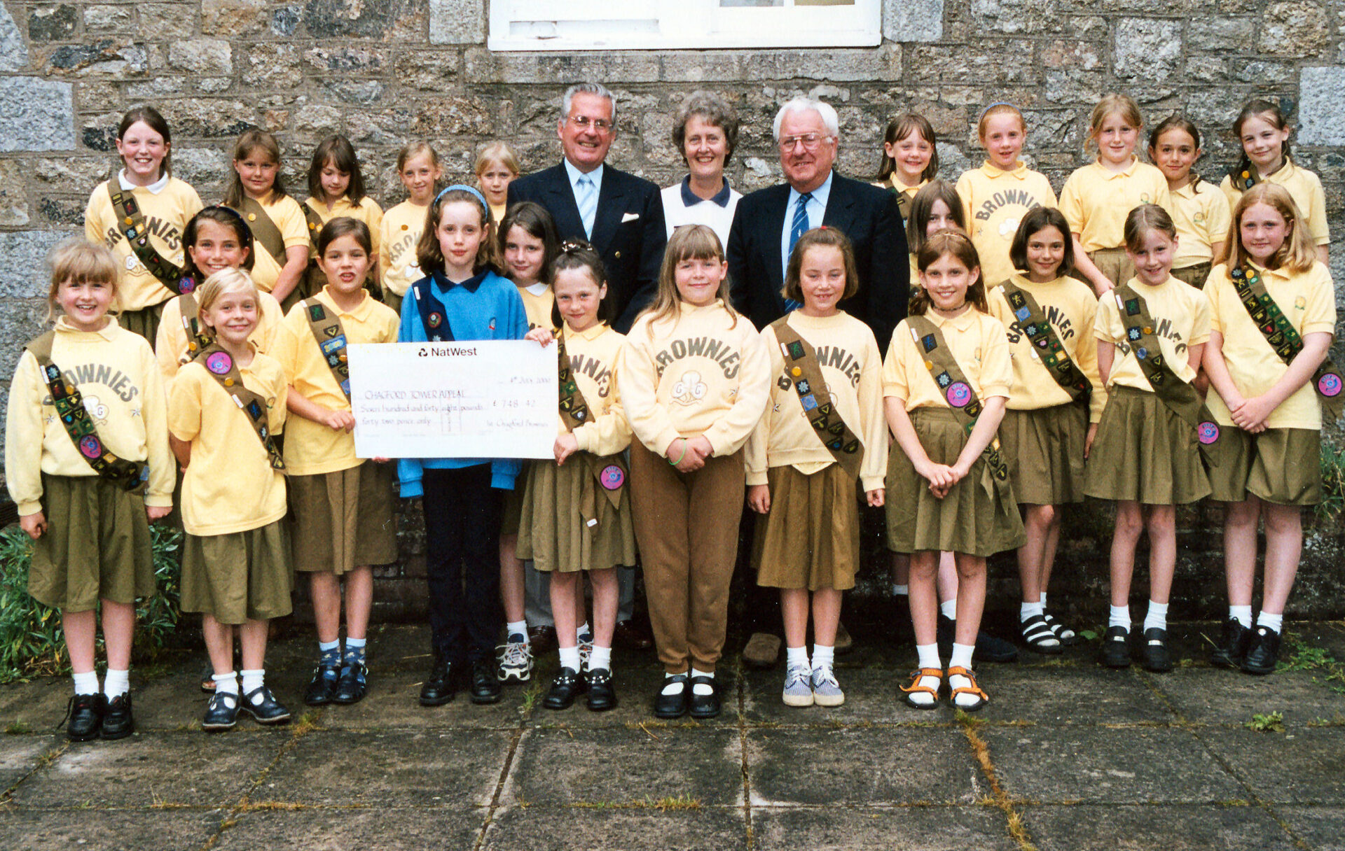 Proud Chagford Brownies presenting a cheque for £748 to members of the Church Tower Appeal Committee in 2000.